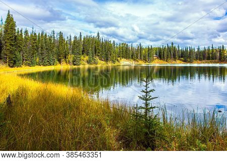 Smooth water reflects the cloudy sky. Quiet shallow lake surrounded by forest and yellow autumn grass. Rocky Mountains of Canada. The concept of ecological, active and photo tourism