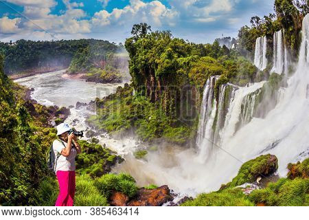 Middle-aged woman in red trousers and panama photographs grandiose waterfalls. Scenic basaltic rock formations famous waterfalls Iguazu Falls. The concept of active and phototourism