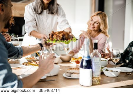 Lady Putting Food On The Festive Table For Her Guests