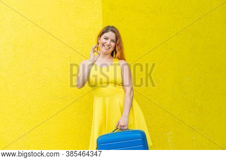 A Red-haired Woman Holds A Blue Bag And Gestures Okay On A Yellow Background.
