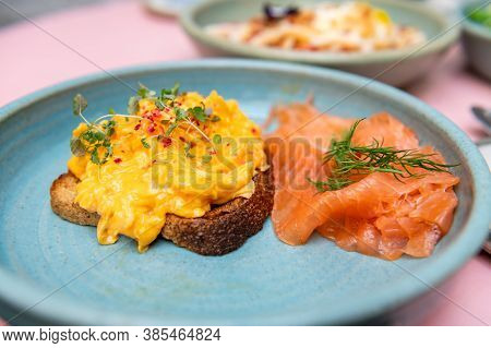 Healthy Breakfast From 3 Scrambled Eggs, Smoked Salmon, Wholemeal Sourdough Bread And Lemon Balm