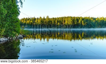 Morning Landscape With A Lake Covered With Haze. Saimaa Lake System, Savo, Finland.