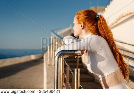Image of redhead young sportswoman looking forward and leaning on railing at sunrise outdoors