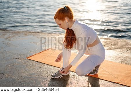 Image of redhead sportswoman in earphones tying up her shoelaces while working out on promenade