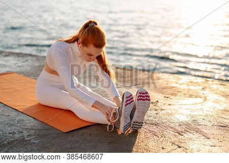 Image of redhead young sportswoman in earphones doing exercise while working out on promenade at sunrise