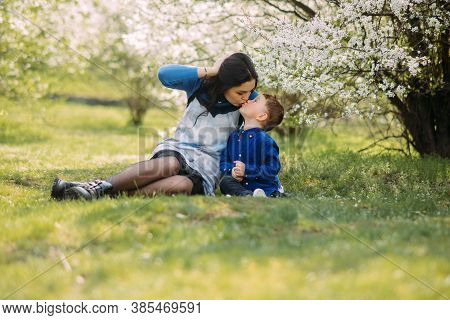 Happy Mother And Son Sit, Rest And Kiss In Green Grass On Sunlit Glade Against Background Of Bloomin