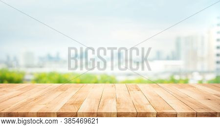 Real Wood Table Top Texture On Blur Leaf Tree Garden And Wall Building From City,park Background.for