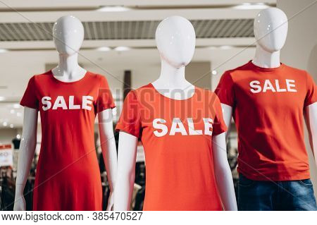 Fashion Mannequins In Red T-shirts And Text Sale Stand In Shop Window And Attract Shoppers. Black Fr