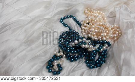 Two Mixed Strands Of Natural White Pearls And Turquoise Imitation Pearls On A White Silk Background.