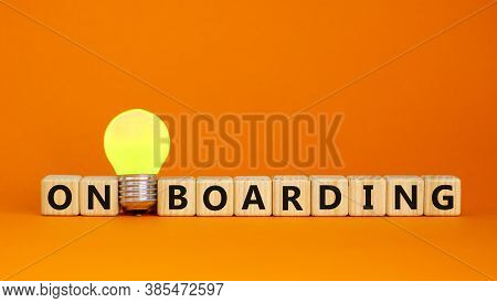 Wooden Cubes With Word 'onboarding'. Yellow Light Bulb. Beautiful Orange Background. Business Concep