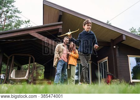 Cheerful Boy Spending Time With Parents Outside The House