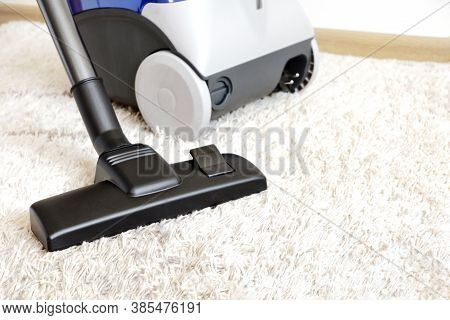 Canister Modern Vacuum Cleaner Blue For Cleaning The House On The Background Of A Soft Beige Carpet.