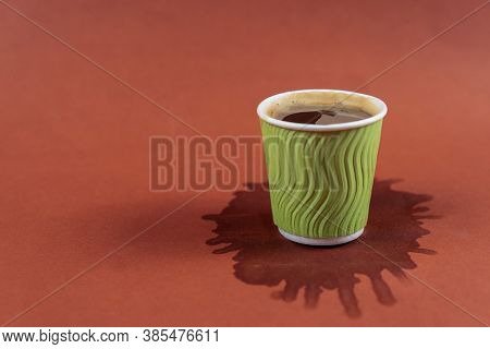 Coffee In Green Paper Cup On Brown Background With Stain. Spilled Espresso On Table. Glass With Amer