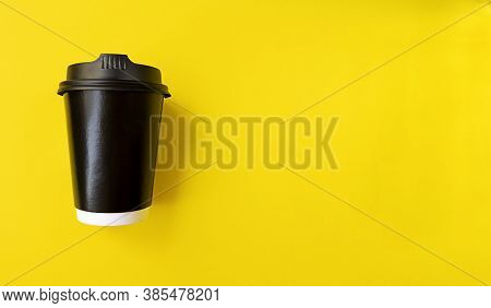 Black Paper Coffee Cup To Go On A Yellow Backgroud. Simple Flat Lay With Copy Space. Minimal Concept