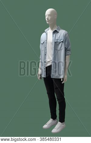 Full-length Male Mannequin Dressed In Blue Shirt And Black Jeans, Isolated On Green Background. No B
