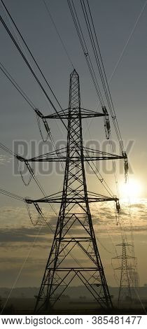 Electricity Pylons Silhouette Fading Into The Distance At Sunrise Across Agricultural Land In Hogges