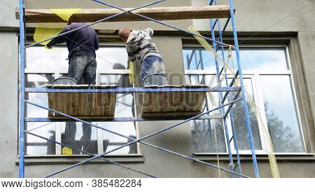 Kyiv, Ukraine - September, 14, 2020: Two Building Contractors On Scaffoldings Are Plastering, Applyi