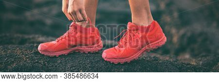 Walking woman tying shoe laces getting ready to walk or run lacing red running shoes banner. Panoramic crop of active person going outside.
