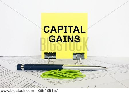 Yellow Sticker With Text Capital Gains Stands On Office Clips. Next To It Is A Blue Pen With Green P