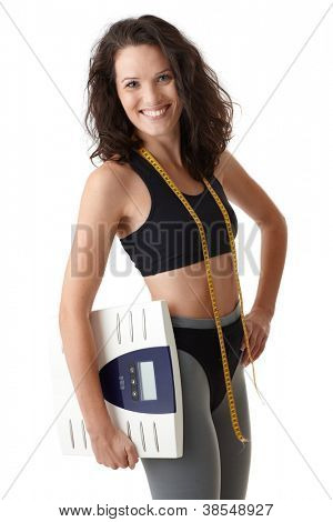Happy sporty woman posing in sportswear with scale and tape measure.
