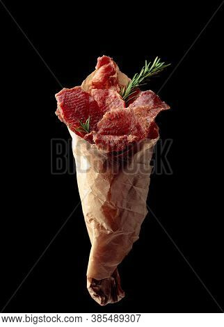 Slices Of Spicy Dry-cured Meat With Rosemary In A Paper Bag Isolated On A Black Background.