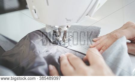 Concept Of Sewing In Modern Bright Studio, Woman In White Sweater Sewing Grey Cloth In Process. Fema