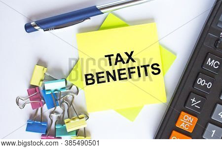 Text Tax Benefits On Yellow Stickers With Calculator, Blue Pen And Paper Clips