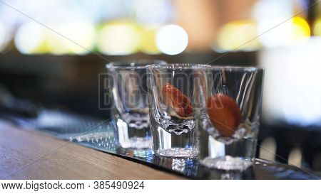 Three Shot Glasses On Bar Counter With Garnish, On Background Of Bokeh Lights. Close Up Shot Of Glas