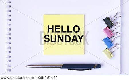 Yellow Sticker With Text Hello Momday Lying On A White Notepad With A Pen And Paper Clips