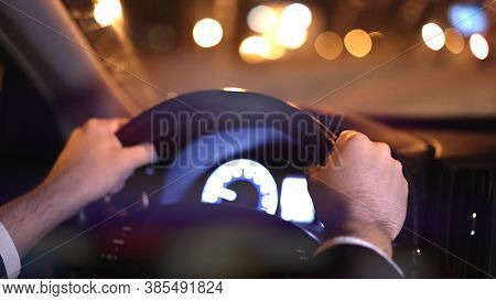 Male Hands On Steering Wheel, Backseat Shot With View On Road At Night. Hands On Wheel, Man In Black