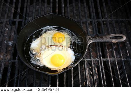 Cast Iron Frying Pan. Eggs being cooked in a Cast Iron Skillet. Frying Pan cooking eggs on a Barbecue Grill.
