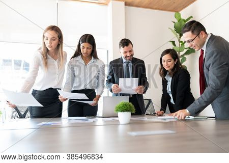 Group Of Male And Female Business Associates With Financial Data Reports During A Meeting In Office