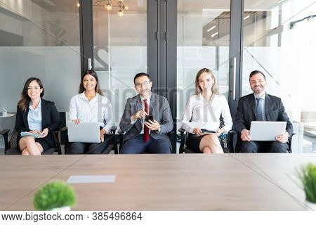 Row Of Multi-ethnic Business People Sitting In Line And Waiting For A Job Interview In Modern Office