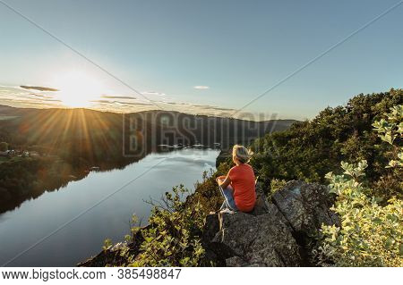 Happy Blonde Girl Sitting On A Rock Enjoying Sunset.beautiful View Of Evening Landscape With A River