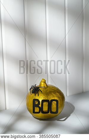 Halloween Decorations. A Painted Golden Pumpkin With The Word Boo And A Spider On A White Wooden Wal
