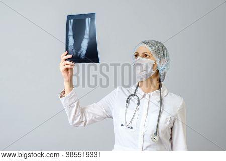 Female Doctor Examining X-ray Image Of Legs Of Newborn Baby
