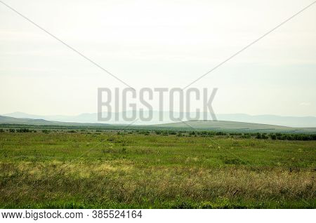 The Endless Steppe Flooded With Bright Sunlight And Mountains In The Background On A Summer Sunny Da
