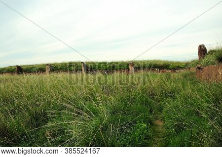Remains Of An Ancient Stone Wall With Tall Grass.