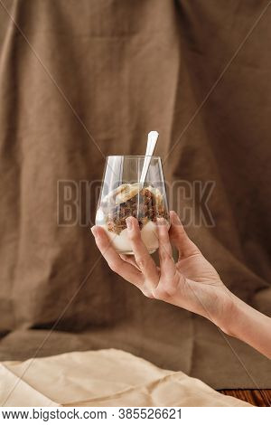Close Up Of Hand Holding Delicious Layered Dessert In Glass Jar, Homemade Yogurt With Granola And Be