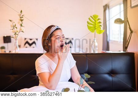 Asian Woman Yawning During On Sofa And Tired Sleepy,female With Symptoms Sleepiness