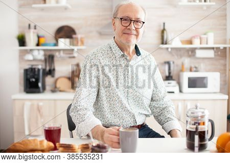 Senior Man In Kitchen Smiling Looking At Camera Holding Hot Coffee Cup. Portrait Of Relaxed Elderly
