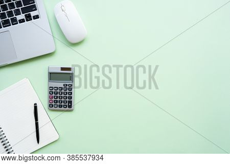 Flat Lay,top View Office Table Desk. Workspace With Calculator, Pen ,laptop , Note On The Pastel Gre