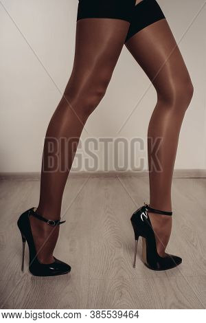 Slender Female Legs In Stockings And A Fetish Shoe With Extremely High Heels. Bdsm Theme.