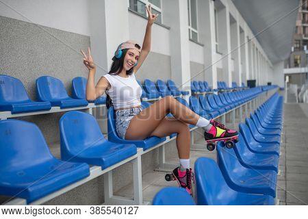 Dark-haired Girl In Roller-skates Listening To Music And Feeling Joyful