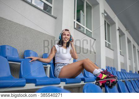 Dark-haired Girl In Roller-skates Listening To Music And Smiling
