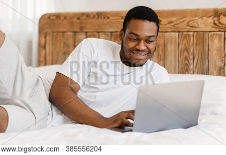 Happy African American Freelancer Man Working On Laptop Computer Browsing Internet Lying In Bed At H