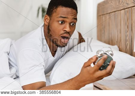 Oversleeping. Overslept African American Man Looking In Shock At Broken Alarm Clock Waking Up In The