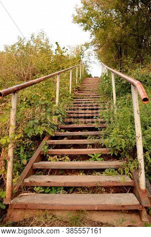Old Wooden Staircase With Iron Railings Thickets Of Trees And Grass.