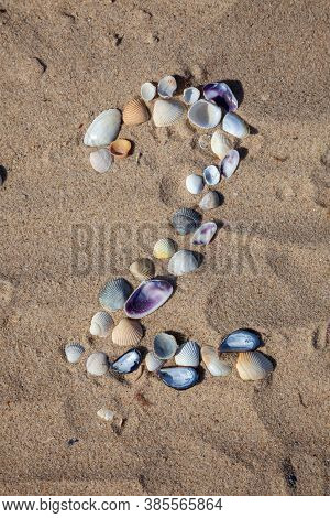 Number 2 Laid Out From Seashells On The Sand. Marine Background. The Symbol Is Two. Shells. Copy Spa