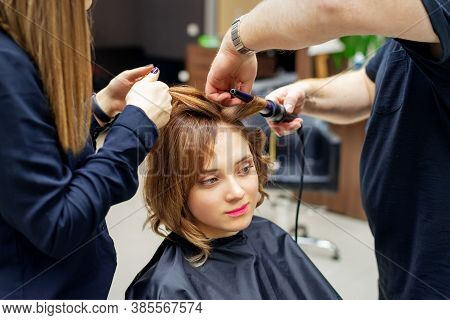 Professional Hairdresser Twists Curls Of Long Light Brown Hair Of Woman With Curling Iron In Beauty